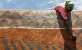 Dona de color pintant un mur