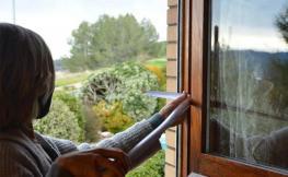dona mesurant finestra