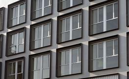 3 pisos de finestres cuadrades d'un edifici gris.