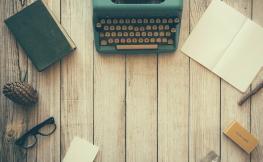 Maquina d'escriure a sobre de taula amb llibretes
