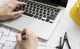 Home teclejant a un ordinador i prenent apunts a un plànol.