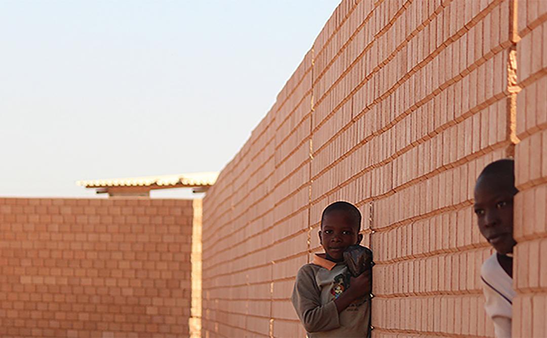 niños mirando al lado de un muro