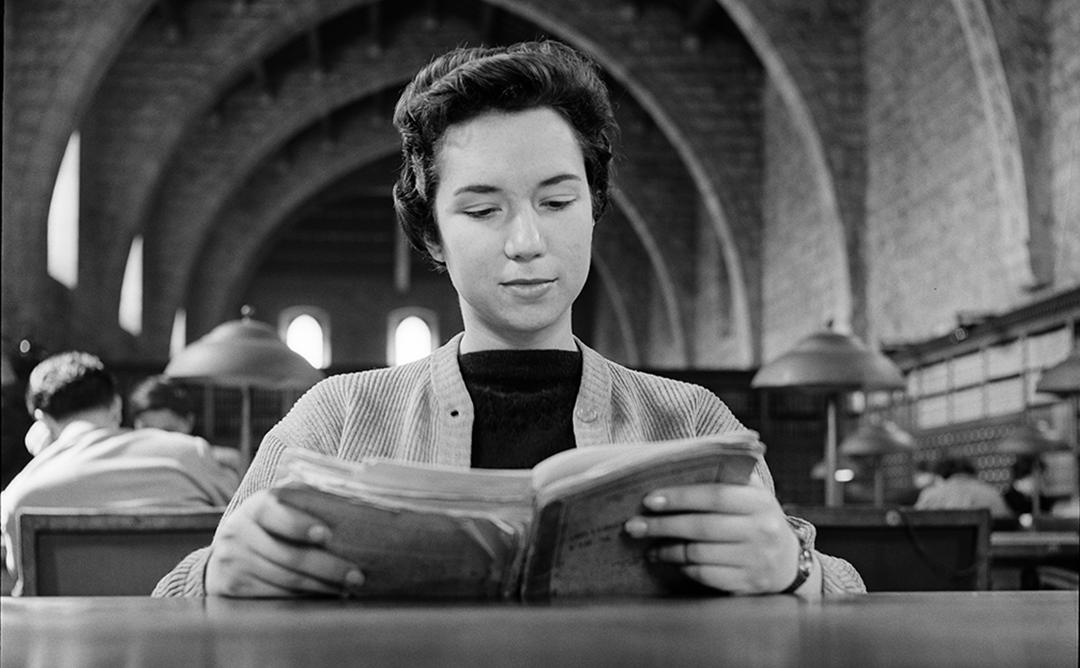 dona llegint a la biblioteca
