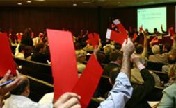 gent fent una votació amb targetes vermelles.