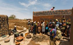 Població africana pintant un mural a una paret