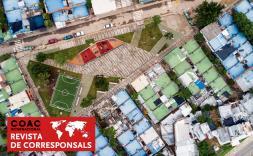 Vista cenital d'un barri amb un camp de futbol.